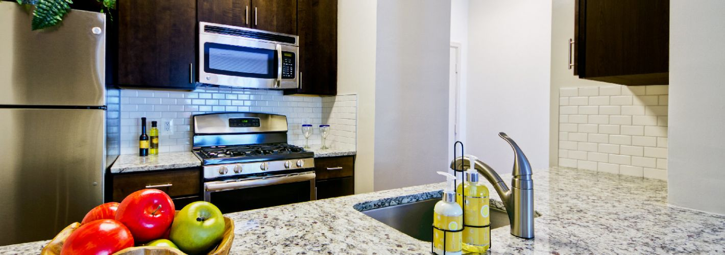 The Courts of Devon : Chef-worthy kitchen with granite countertops and stainless steel appliances